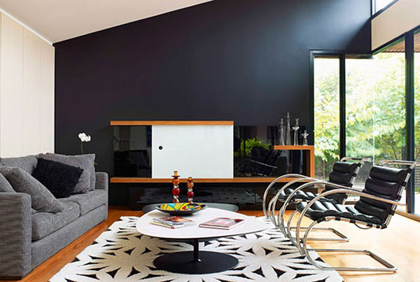 Spacious-room-with-black-wall-and-stylish-grey-sofa-and-unqiue-white-table-with-cool-arm-chairs